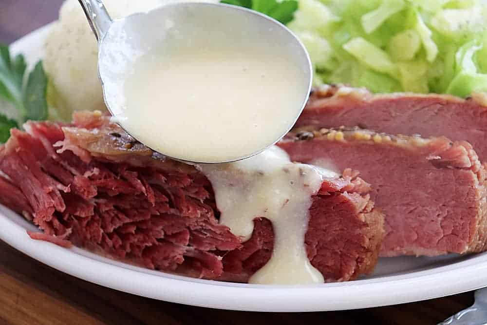 Drizzling sauce over corned beef