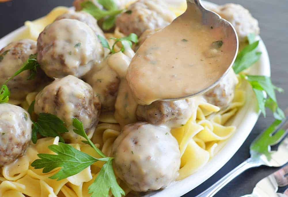 Ladeling sauce over meatballs and noodles